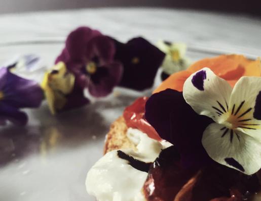 bruschetta con burrata, pomodorini confit e viole del pensiero