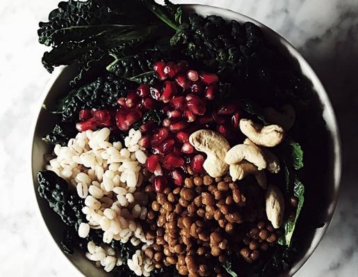 Un Buddha Bowl di cavolo nero, orzo, lenticchie e anacardi con una vinaigrette al melograno e miele.